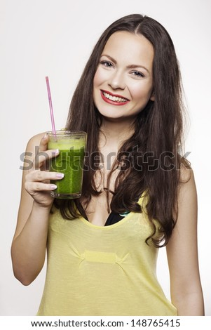 Go green. Young beautiful woman enjoying a healthy raw fruit vegetable juice. Studio shot. - stock photo