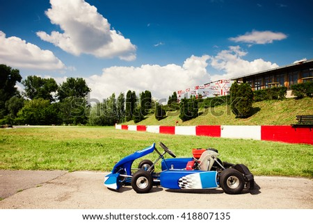 go-kart car parked next to track side view - stock photo