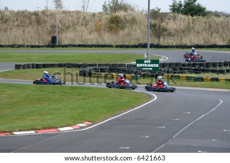 Go kart drivers race past the pit stop entrance and speed around the track