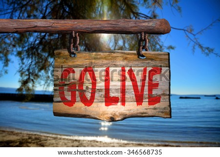 Go live motivational phrase sign on old wood with blurred background