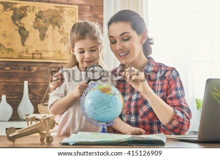 Go on an adventure! Happy family preparing for the journey. Mom and daughter study the map and choose a route of travel. - stock photo