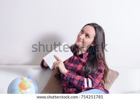 Go on an adventure. Pretty woman dreaming about traveling around the world, making notes in a diary with countries for travel. Happy cute brunette preparing for the journey.