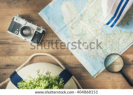 Go on an adventure! The map and the camera on a wooden table. Top view. - stock photo