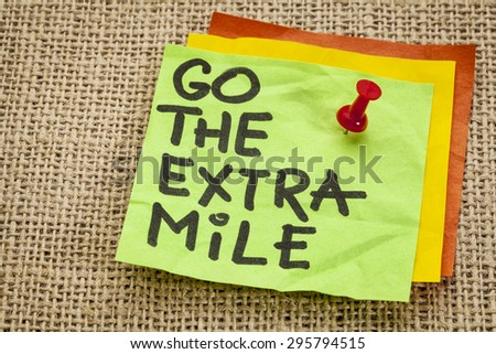 go the extra mile  - motivational reminder - handwriting on sticky note - stock photo