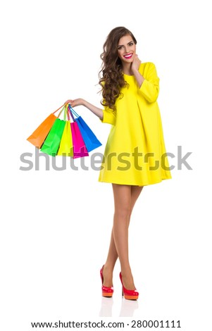 Go to Shopping. Smiling elegance young woman in red high heels and yellow mini dress standing and holding colorful shopping bags. Full length studio shot isolated on white. - stock photo