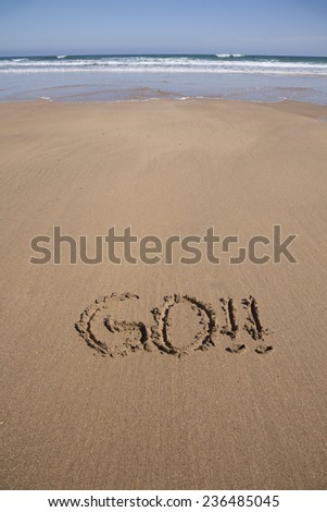 go word written on brown sand ground low tide beach ocean seashore in Spain Europe - stock photo