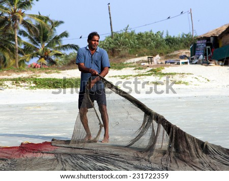 GOA, INDIA - FEB 13, 2014: Indian fisherman pulling fishing nets. Fishing is a key occupation on coast of Indian ocean - stock photo