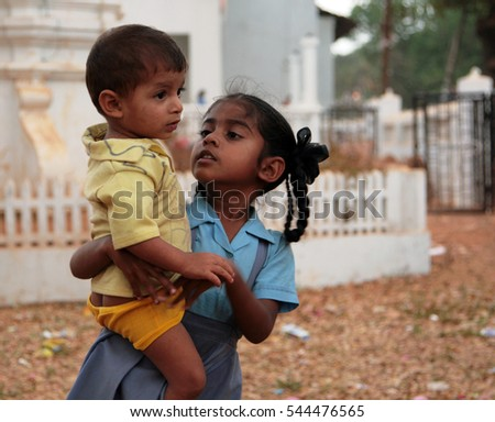 GOA, INDIA - FEB 10, 2013: Indian girl with her younger brother