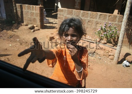 Goa, India - February 02, 2006:An unidentified beggar girl begs for money from tourist . Poverty is a major issue in India. - stock photo