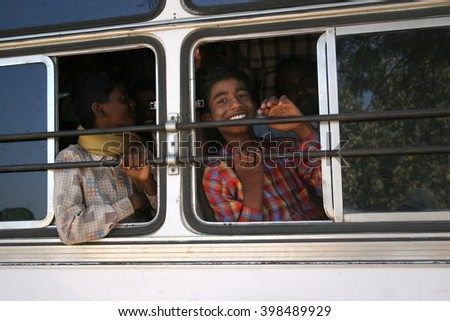 Goa, India - February 05, 2006: People in the indian bus. A boy smiles throught the bus window