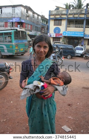 Goa, India - February 11, 2006: Unknown Indian woman is with a baby  on the street of Chaudi.