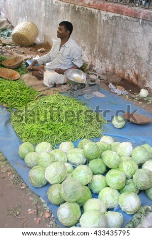 Goa, India - February 11, 2006:  Vegetable seller looks for customers. The Market in Chaudi.