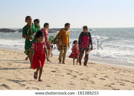 GOA, INDIA - JAN. 10,2014: Unknown family with the children stroll along the beach in Goa, India on JAN. 10, 2014