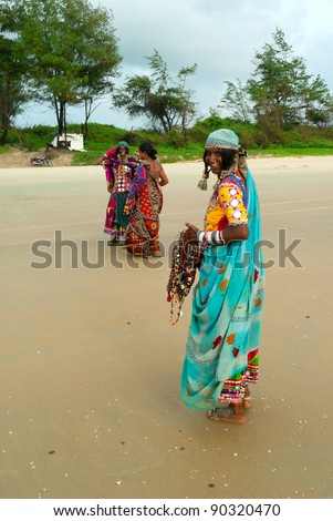 GOA, INDIA - SEPTEMBER 18: Unidentified Indian women and children in traditional dress pose for tourist photos on Goa beach, September 18, 2011 in Goa, India. This activity will provide a income stream for poor women on this Indian state