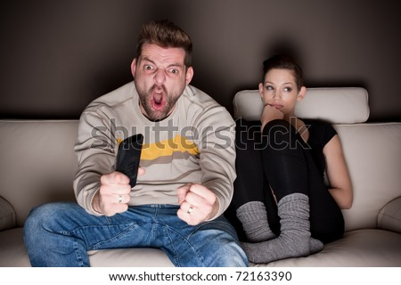 Goaaaaal! A man watching football, while his girlfriend is sitting besides him bored. Showing the differences between the sexes. - stock photo