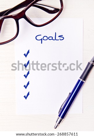 goal checklist on desktop with office supplies - stock photo