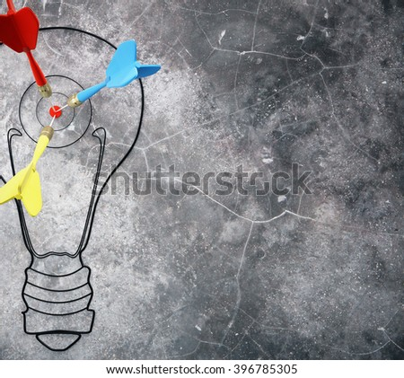 Goal concept with light bulb and darts on dark concrete wall. Mock up - stock photo