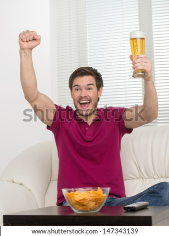 Goal! Happy young men holding a beer glass in his hand and expressing positivity - stock photo