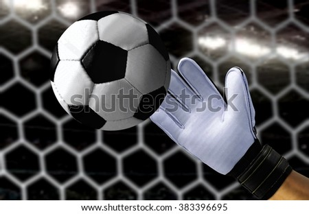 Goal keeper trying to catch a fast soccer ball - stock photo