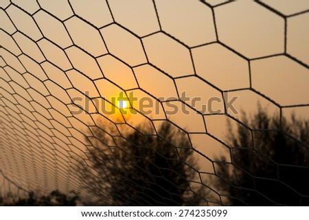 Goal net in the sunset - stock photo