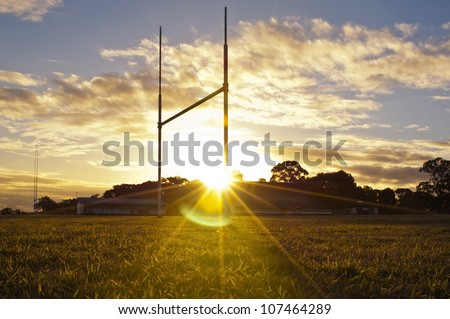 Goal posts for football, rugby union or league on field at sunset - stock photo