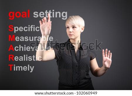Goal setting concept - business woman touching screen - stock photo