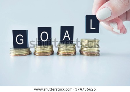 Goal text stacked on coins with cool image temperature as financial concept - stock photo