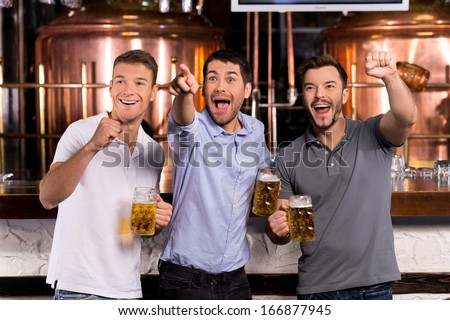 Goal! Three happy men holding beer mugs and gesturing while watching TV in bar  - stock photo