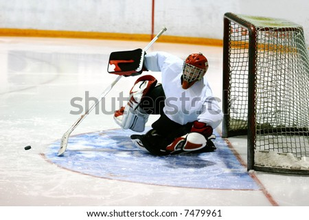 Goalie in generic white jersey with generic red goalie mask makes a tremendous diving attempt to prevent the puck (frozen in flight) from entering the goal