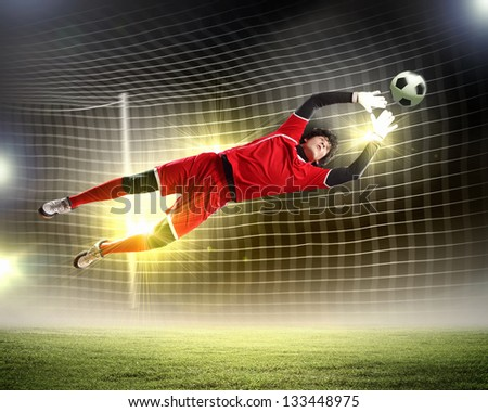 Goalkeeper catches the ball . At the stadium, in the spotlight. - stock photo