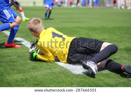 Goalkeeper catching ball and falling on grass - stock photo
