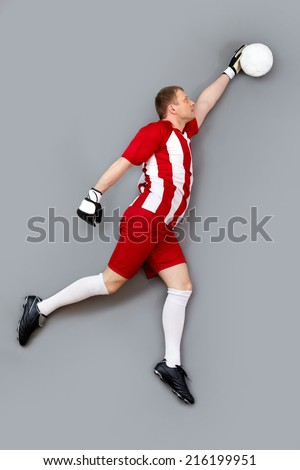 Goalkeeper catching the ball over grey background - stock photo