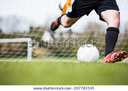 Goalkeeper kicking ball away from goal on a clear day - stock photo
