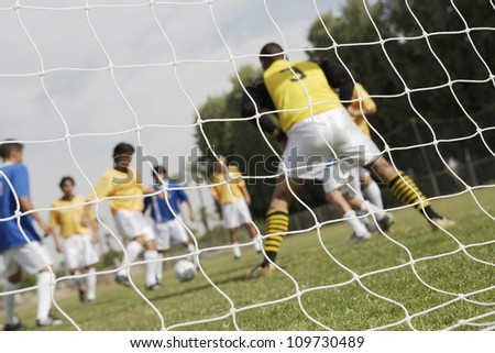 Goalkeeper ready to save a shot with striker preparing to shoot in the background - stock photo