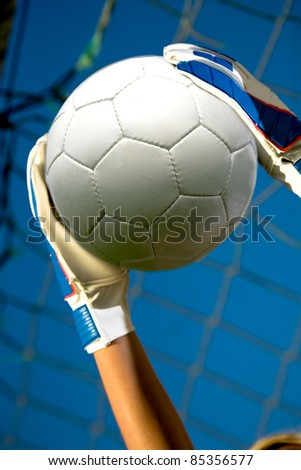 goalkeepers hands holding a soccer ball - stock photo