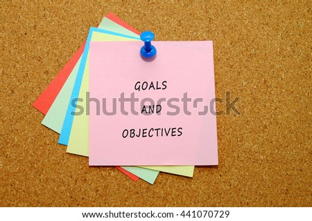 Goals and Objectives written on color sticker notes over cork board background. - stock photo