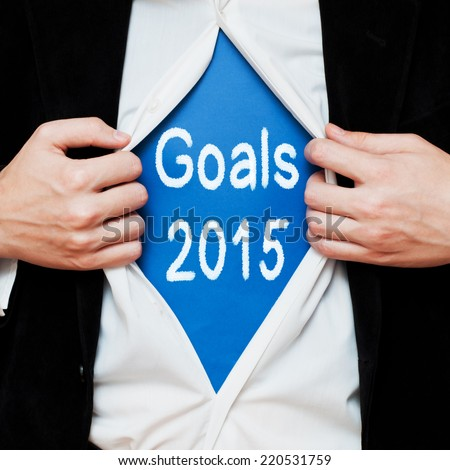 Goals 2015. Businessman showing a superhero suit underneath his shirt with a message text written on it. - stock photo