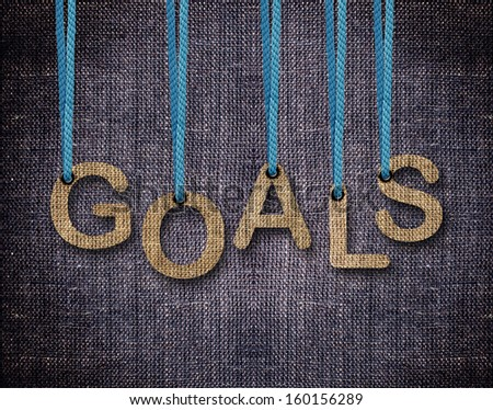Goals Letters hanging strings with blue sackcloth background. - stock photo
