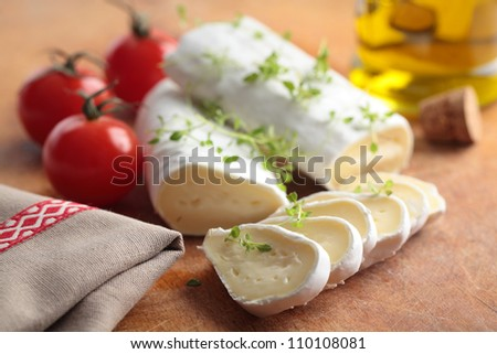 Goat cheese, cherry tomato, and thyme on a wooden cutting board - stock photo