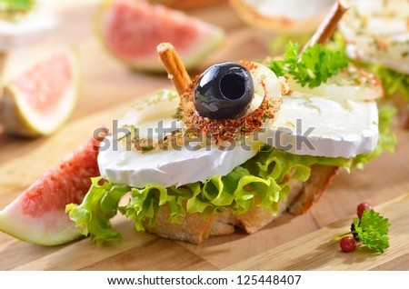 Goat cheese on baguette with spiced onion rings, olives, lettuce and pretzel sticks
