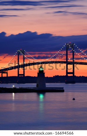 Goat Island Lighthouse, Newport RI, at Sunset with Claiborne Pell Bridge in the Background Vertical - stock photo