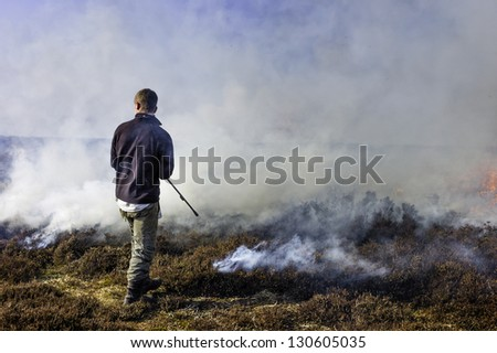 GOATHLAND, UK - MARCH 06: Unidentified moorland management employee sets fire to  heather to help invigorate fresh growth on March 06, 2013 in the North York Moors near Goathland, Yorkshire, UK.