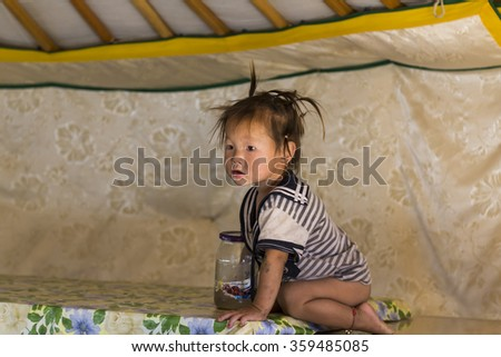 Gobi Desert, Mongolia. August 2015 - A Mongolian Baby playing on top of a table inside a ger.