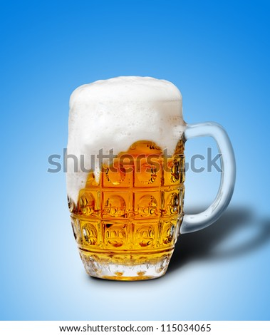 goblet of light beer foam. lager beer in a glass beaker with fresh bubbling foam. alcoholic fresh beverage  yellow color. pub drink. blue background - stock photo