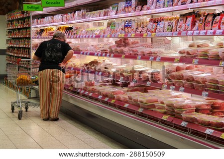 GOCH, GERMANY - MAY 6: Customer selecting packaged meat in refrigerated section of a Kaufland hypermarket. Photo taken on May 6, 2015 in Goch, Germany - stock photo