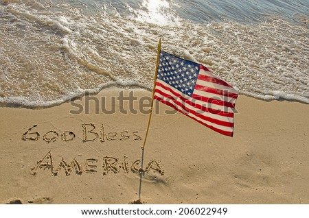 God Bless America written in beach sand with American flag - stock photo