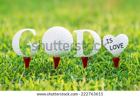 GOD IS LOVE, Golf letters word on green grass. - stock photo