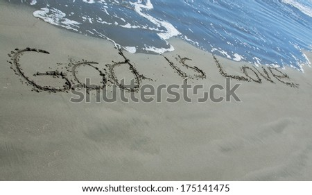 God is Love written in sand as the waves wash close to it. - stock photo