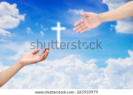 god's hands giving white cross for rescue human on blurred sky backgrounds.hands isolated on blurred backgrounds. - stock photo