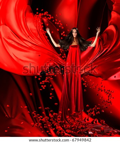 goddess of love in long red dress with magnificent hair makes a magic ritual of connecting hearts of people on red drapery, fabric